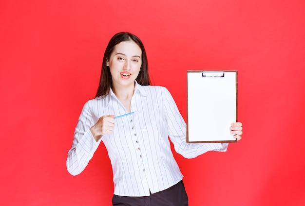 Jonge positieve zakenvrouw die leeg klembord houdt en poseert.