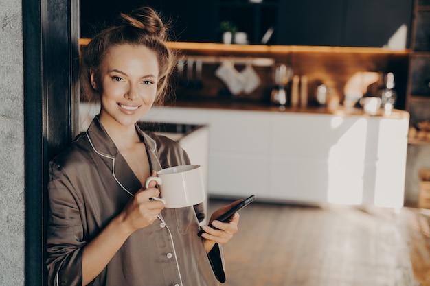 Jonge positieve zakenvrouw draagt een zijden bruine pyjama die lacht terwijl ze de smartphone in de hand houdt en koffie drinkt nadat ze 's ochtends thuis wakker wordt voordat ze naar haar werk gaat, in de slaapkamer staat
