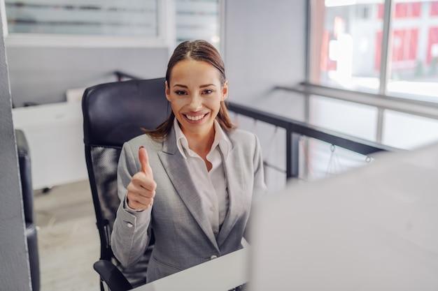Jonge prachtige aantrekkelijke kaukasische glimlachende zakenvrouw in pak
