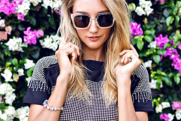 Jonge prachtige blonde jonge vrouw, stijlvolle outfit, trendy sprankelende crop top en zonnebril dragen, poseren in bloementuin
