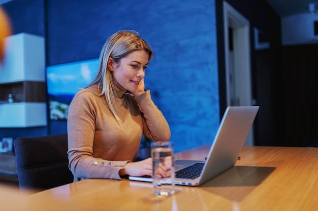 Jonge prachtige blonde vrouwelijke ondernemer om thuis te zitten en met behulp van laptop tijdens covid 19 uitbraak.
