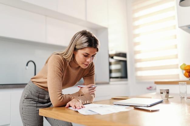 Jonge prachtige blonde zakenvrouw leunend op de keukentafel en rekeningen opvullen terwijl je in de keuken thuis staat.