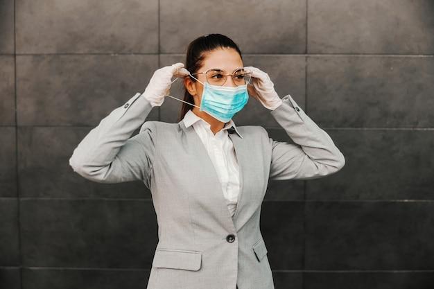 Jonge prachtige brunette gekleed smart casual permanent buitenshuis en gezichtsmasker zetten tijdens uitbraak van het covid-virus.