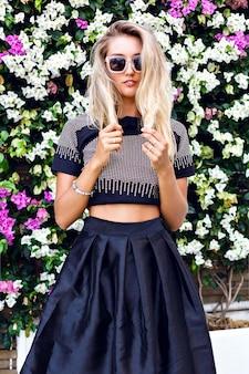 Jonge prachtige prachtige blonde jonge vrouw, gekleed in een stijlvolle outfit, midi-rok, trendy sprankelende crop top en zonnebril