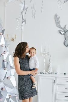 Jonge, prachtige vrouw in een modieuze jurk houdt haar schattige zoon in haar handen in het interieur dat is versierd voor het nieuwjaarsfeest