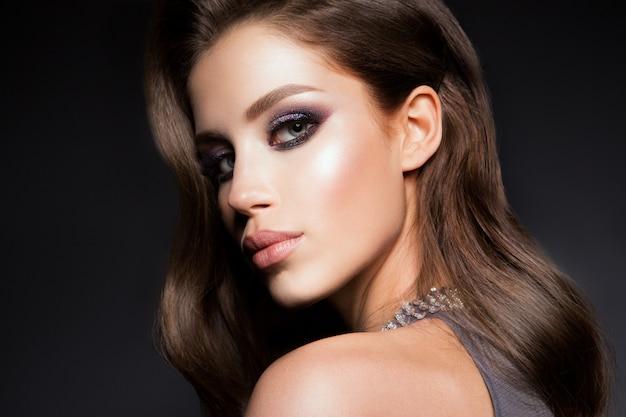 Jonge prachtige vrouw in luxe jurk.