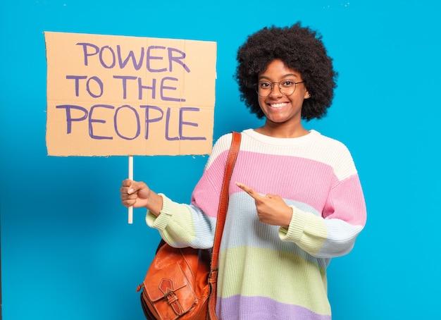 Jonge pre-afrovrouw die protesteert met een macht aan de mensenbanner