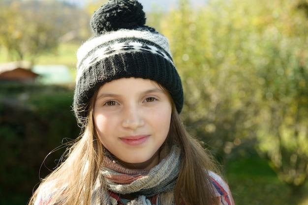 Jonge pre-tiener met een wintermuts, buitenshuis