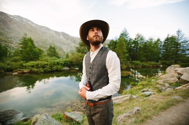Jonge predikant die heilige bijbel vasthoudt en naar de bergen kijkt