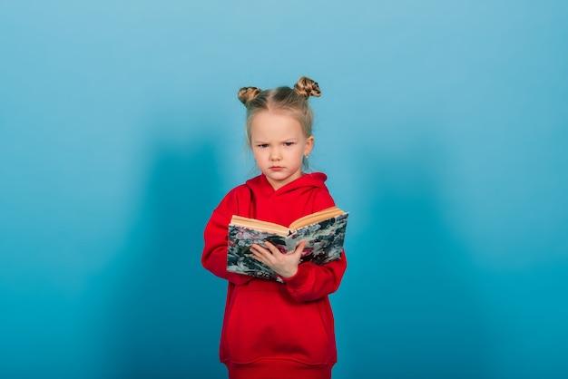 Jonge preschool kind leert tijdens het lezen van een boek, geïsoleerd op blauw