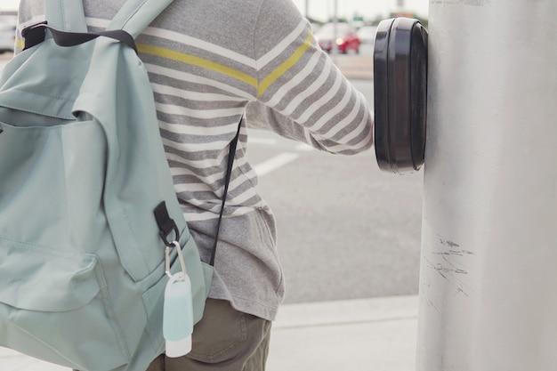 Jonge preteen tween tienerjongen student met behulp van zijn elleboog op verkeerslichtknop te drukken