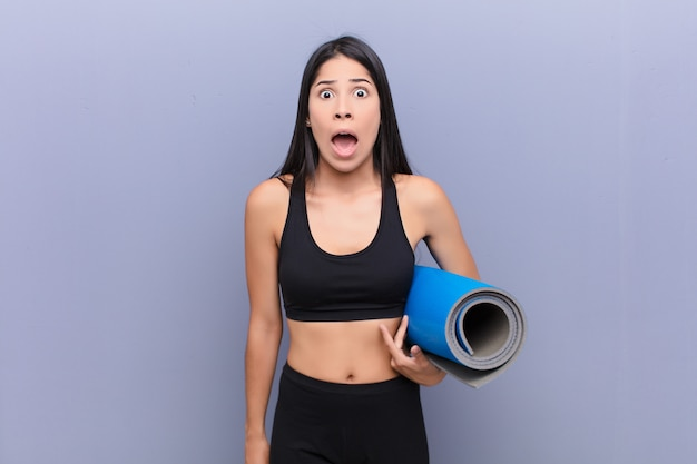 Jonge prettygvrouw met een yogamat over cementmuur