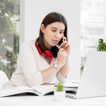 Jonge privé-leraar die thuis haar mobiele telefoon en laptop met behulp van