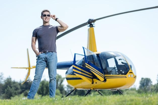 Jonge professional. knappe luchtpolitieagent inspecteert helikopterplatform en glimlachend tevreden terwijl poseren voor een helikopter