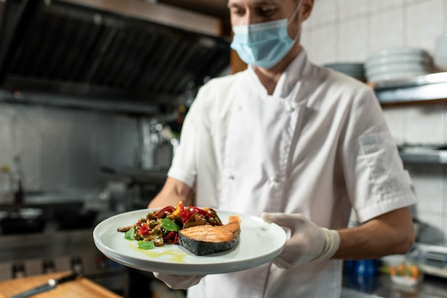 Jonge professionele chef-kok in wit uniform en beschermend masker en handschoenen met bord met gebakken zalm en groentegarnituur in de keuken