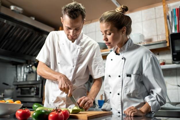 Jonge professionele chef-kok met mes die zijn vrouwelijke stagiair laat zien hoe hij verse courgette moet koken terwijl ze allebei aan tafel in de keuken van het restaurant staan