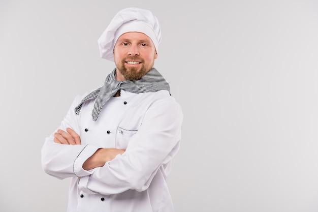 Jonge professionele chef-kok van restaurant met zijn armen gekruist door de borst op zoek naar jou met brede glimlach