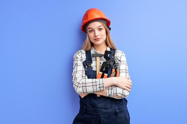 Jonge professionele dienstvrouw die oranje helm en de blauwe hulpmiddelen van de overallholding draagt