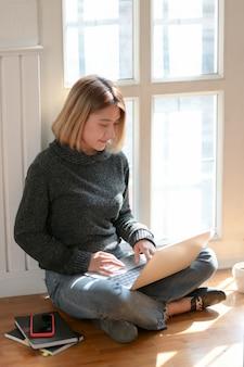 Jonge professionele freelancer werkt aan haar project tijdens de vergadering in de buurt van de ramen