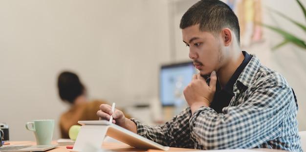 Jonge professionele grafisch ontwerper die aan het project werkt