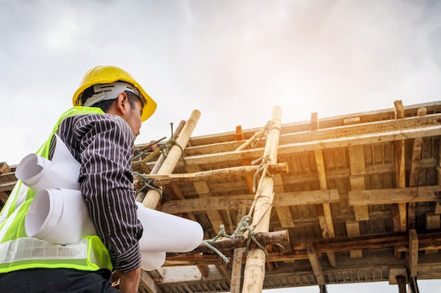 Jonge professionele ingenieur werknemer in beschermende helm en blauwdrukken papier bij de hand bezig met ladder op de bouwplaats van het huis