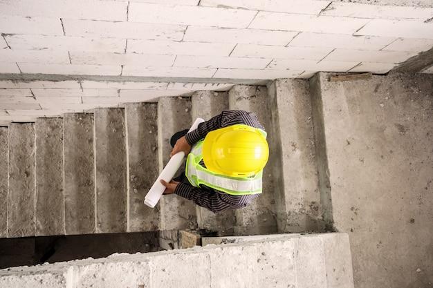 Jonge professionele ingenieur werknemer in beschermende helm en blauwdrukken papier bij de hand op de bouwplaats van het huis