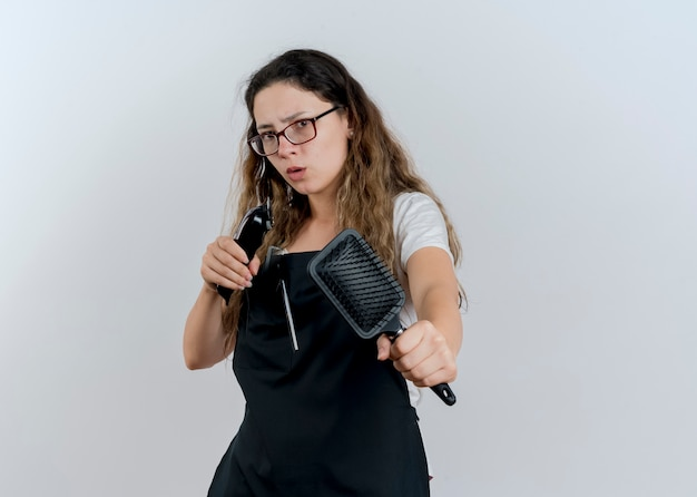 Jonge professionele kapper vrouw in schort bedrijf trimmer en haarborstel front wordt bezorgd staande over witte muur kijken