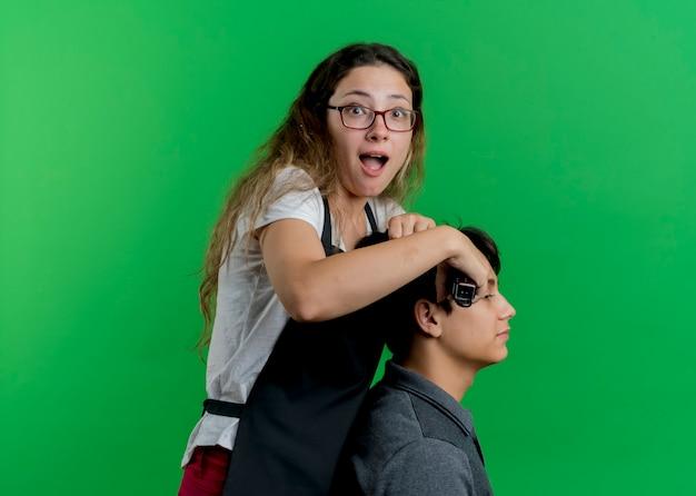 Jonge professionele kapper vrouw in schort knippen haar met trimmer van man client, kijken naar voorkant wordt verrast staande over groene muur