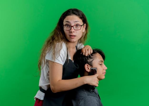 Jonge professionele kapper vrouw in schort knippen haar met trimmer van man client, verrast