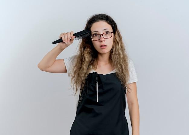 Jonge professionele kapper vrouw in schort met haarborstel haar haren kammen kijken naar voorkant verward staande over witte muur