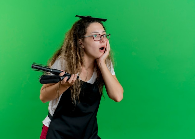Jonge professionele kappervrouw die in het haarborstels van de schortholding opzij kijken wordt verbaasd status over groene muur