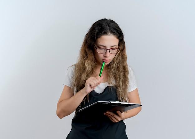 Jonge professionele kappervrouw die in het klembord en de pen van de schortholding het met peinzende uitdrukking bekijkt die zich over witte muur bevindt