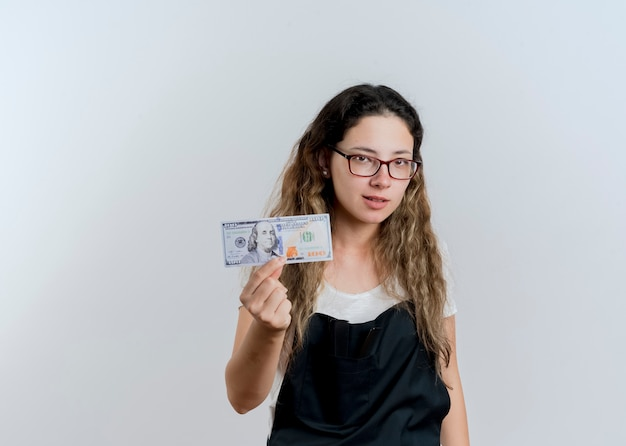 Jonge professionele kappervrouw die in schort geld toont die voorzijde met ernstig gezicht bekijkt dat zich over witte muur bevindt