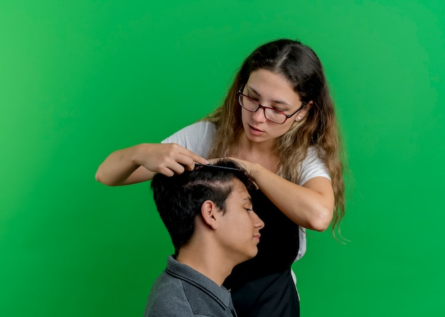 Jonge professionele kappervrouw die in schort haar van mensencliënt kammen die zich over groene muur bevinden
