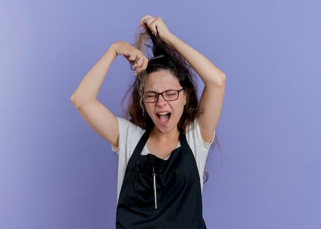 Jonge professionele kappervrouw die in schortschaar houdt die haar haar probeert te knippen schreeuwend met geïrriteerde uitdrukking die zich over blauwe muur bevindt