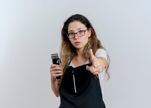 Jonge professionele kappervrouw in de trimmer die van de schortholding met wijsvinger aan voorzijde richt die zich zelfverzekerd over witte muur bevinden