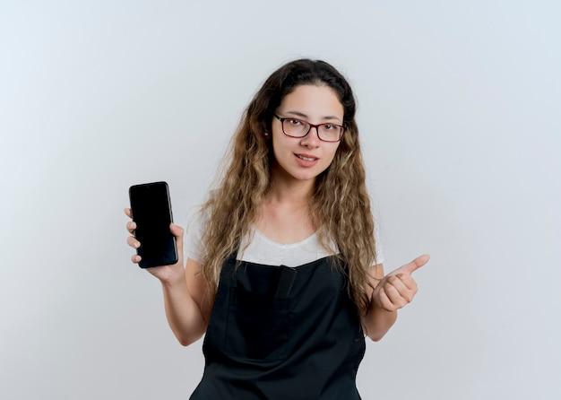 Jonge professionele kappervrouw in schort die smartphone het glimlachen tonen die voorzijde bekijken die duimen tonen die zich over witte muur bevinden
