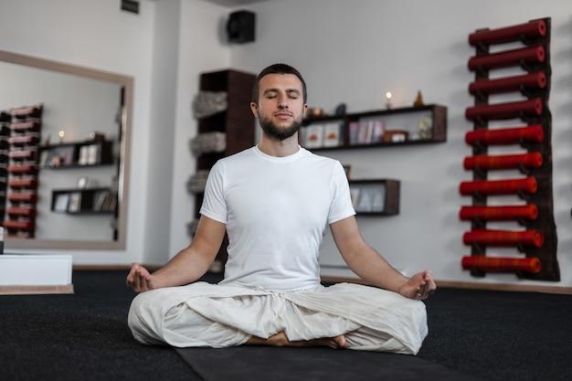 Jonge professionele man die binnenshuis mediteert. gezonde levensstijl. yoga tijd.