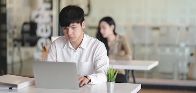 Jonge professionele mannelijke ontwerper die aan zijn project werkt terwijl het gebruiken van laptop computer