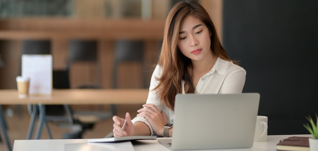 Jonge professionele onderneemster die aan haar project met laptop werkt