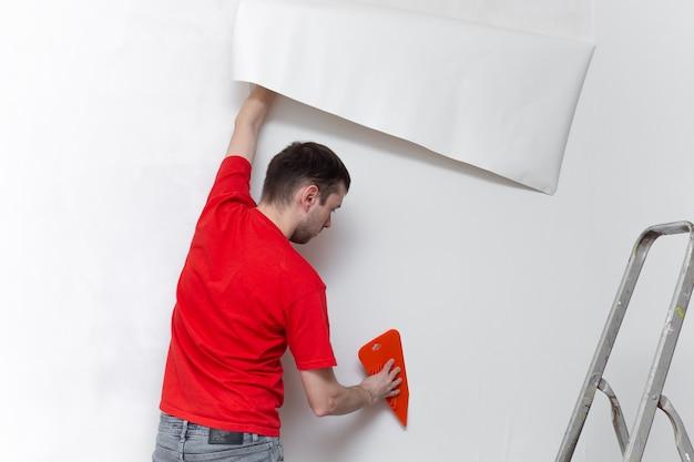 Jonge professionele reparateur die behang op betonnen muur lijmt