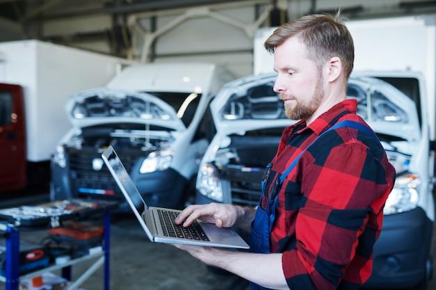 Jonge professionele reparateur van auto servicecentrum met behulp van laptop tijdens het surfen op de website of het opnemen van online bestellingen