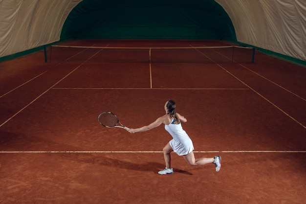 Jonge professionele sportvrouw tennissen op de muur van het sportveld Gratis Foto