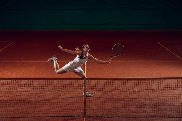 Jonge professionele sportvrouw tennissen op de muur van het sportveld