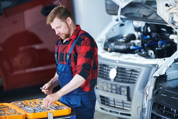 Jonge professionele technicus die een van de handgereedschappen uit de gereedschapskist neemt tijdens het kiezen van een voor reparatie van de motor van een auto