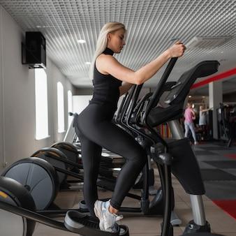 Jonge professionele trainer vrouw in zwarte sportkleding in gymschoenen houdt zich bezig met een stepper-simulator in een fitness-studio
