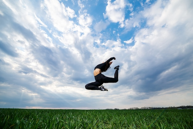 Jonge professionele turnster springt in de natuur tegen de blauwe lucht. meisjesatleet in een zwarte top en zwarte legging doet acrobatische oefeningen