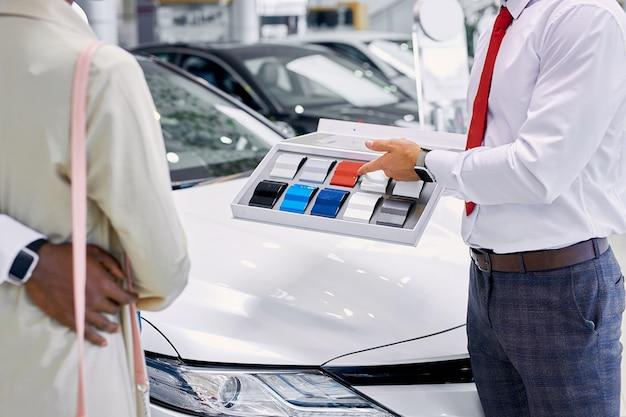 Jonge professionele verkoper vertegenwoordigt een kleurenpalet voor kopers