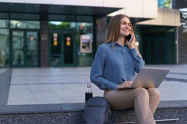 Jonge professionele vrouw zittend op de trap voor glazen gebouw, laptop op schoot houden en praten op mobiele telefoon