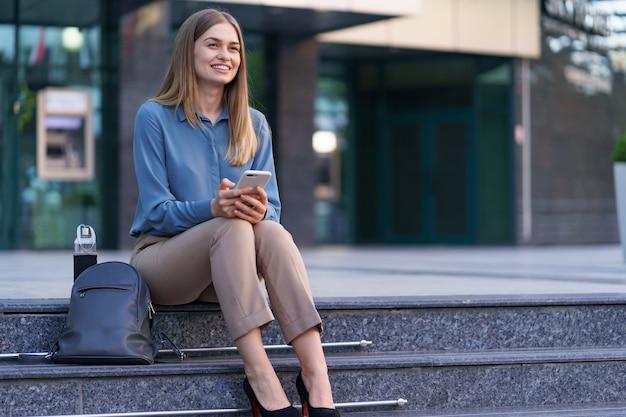 Jonge professionele vrouw zittend op de trap voor glazen gebouw, praten op een mobiele telefoon